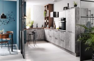 Betonlook keuken in L vorm met bureau dan wel bar aan de muur – Grijze moderne keuken Häcker Comet