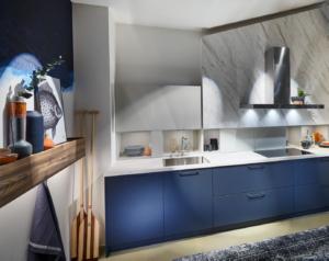 Moderne blauwe keuken met Carrara marmerlook schouw, Häcker keuken AV 6000 fluweel blauwe keukendeurtjes en ladefronten + plint, RAL zijdegrijs, lariks houten keukenbak
