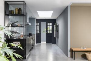 Zwarte industriële keuken met blauwgrijze tegel achterwand, Muren geverfd met Flexa Brave Ground en blauw/grijs tinten)